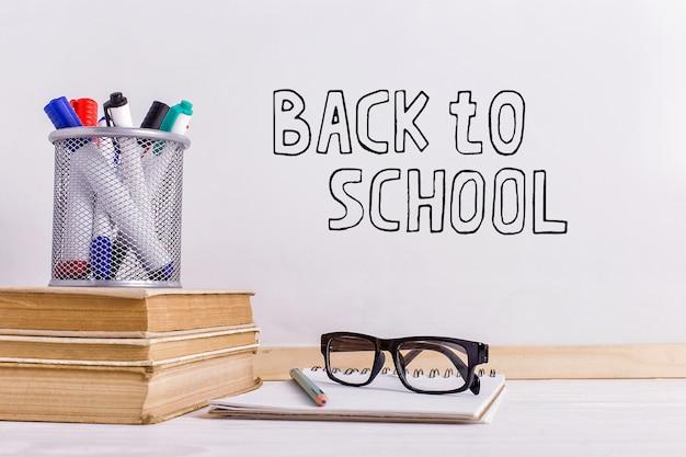 Le marqueur d'inscription sur un tableau blanc, retour à l'école une table avec des livres et des attributs de lunettes pour l'écriture.