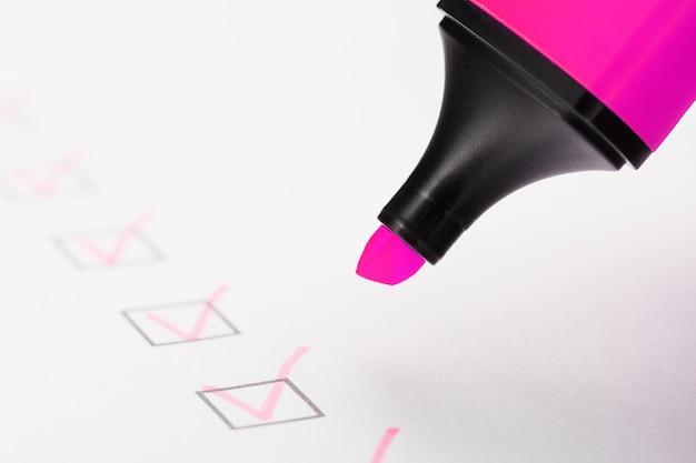 Un marqueur magenta avec des marqueurs sur la feuille de contrôle. liste de contrôle du concept de tâche terminé.