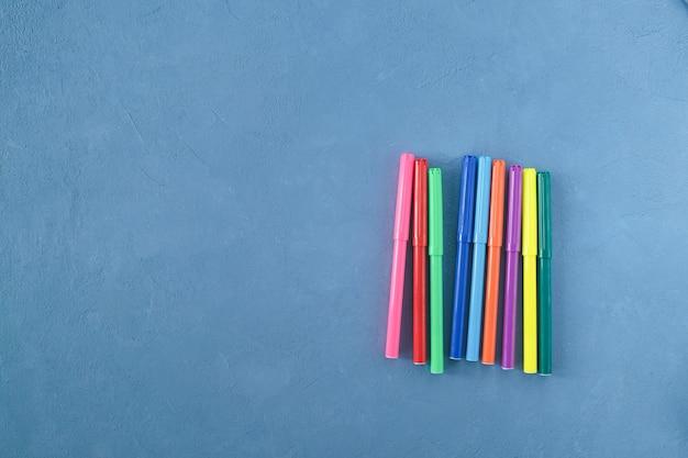 Marqueurs colorés sur une vue de dessus de fond bleu