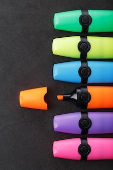 Marqueurs de différentes couleurs sur fond noir.