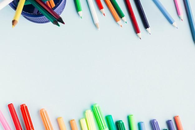 Des marqueurs lumineux et des crayons sur fond blanc