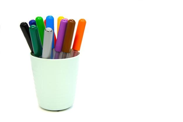 Marqueurs multicolores dans une tasse en plastique isolé sur un mur blanc