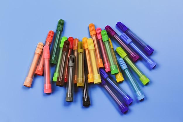Marqueurs multicolores de différentes nuances sur fond bleu.