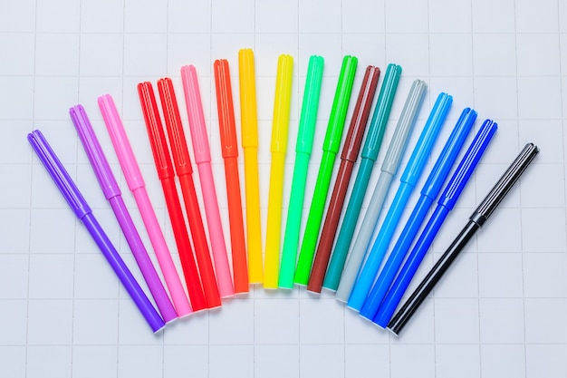 Marqueurs multicolores sur fond de papier quadrillé blanc.