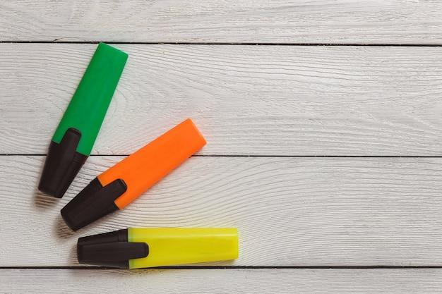 Marqueurs surligneur jaunes, verts et orange sur bois blanc