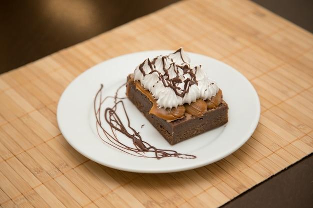 Marquise gâteau au chocolat façon brownie garni d'une couche de dulce de leche et d'une autre couche de meringue. en plaque blanche sur tapis en bois