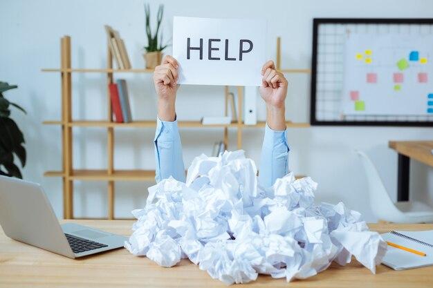 Marre. travailleur expérimenté assis sur son lieu de travail et levant les bras tout en démontrant de la merde de papier avec un mot dessus