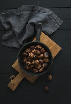 Marrons grillés dans une poêle en fer sur une planche en bois rustique au-dessus d'un tableau noir, vue de dessus.