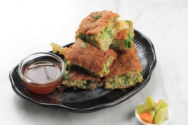 Martabak telur est une cuisine de rue populaire en indonésie. oeuf, oignon de printemps enveloppé d'une pâte à la farine mince