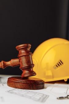 Marteau en bois et casque jaune avec l'image verticale de plans de construction