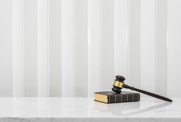 Marteau en bois et livre de droit mis sur le comptoir de table en marbre blanc