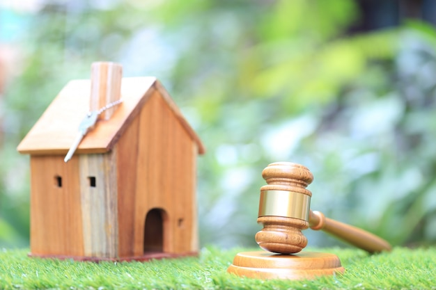 Marteau en bois et maison modèle sur fond vert naturel
