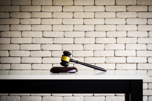 Marteau en bois sur une table blanche. affaires de juge ou fond d'enchères.