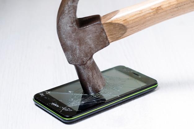 Le marteau brise l'écran du smartphone posé sur la table.
