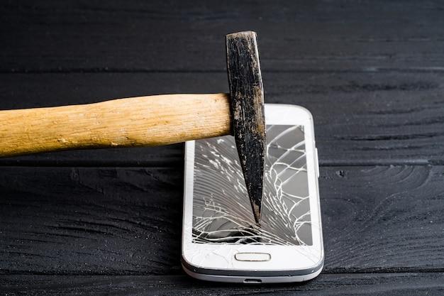 Marteau brise le smartphone sensoriel moderne isolé sombre. cher téléphone portable brisé par un gros marteau sur une surface en bois.