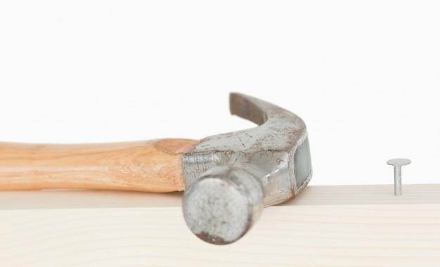 Un marteau et un clou enfoncé sur une planche de bois