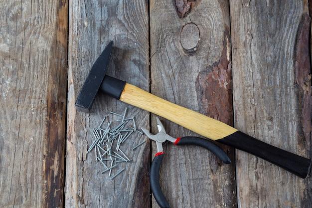 Marteau, clous et pinces sur une table en bois