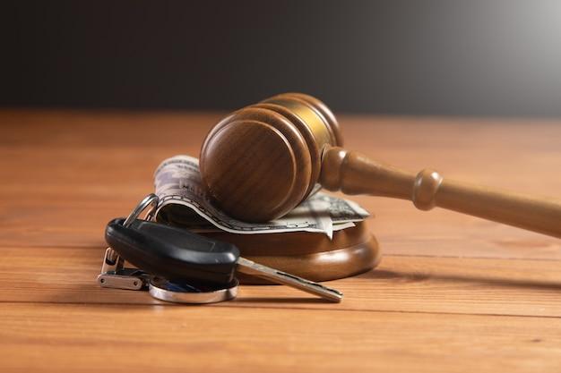 Marteau de la cour avec de l'argent et des clés de voiture sur la table