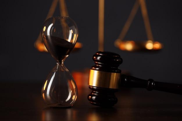 Marteau du juge, balance de la justice et sablier dans une pièce sombre.