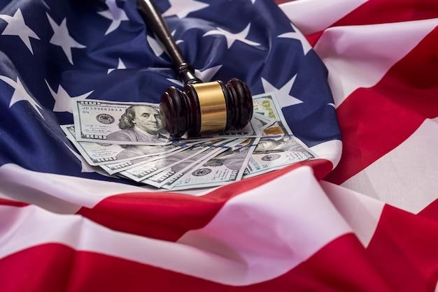 Marteau du juge avec des billets en dollars sur le drapeau américain