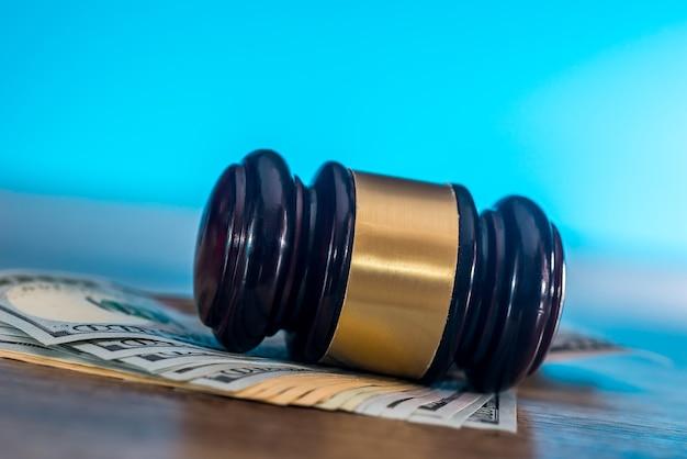 Marteau du juge avec des dollars en rouleau et des pièces d'or