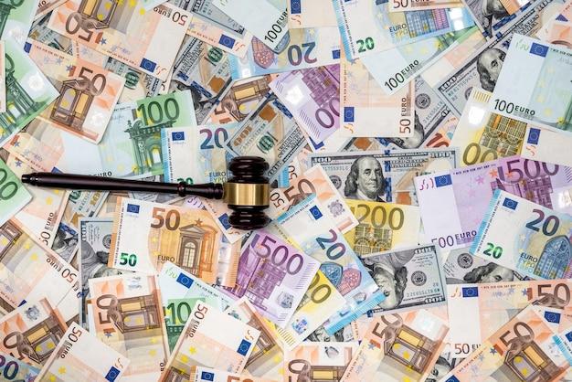 Marteau du juge sur fond de billets en dollars et en euros