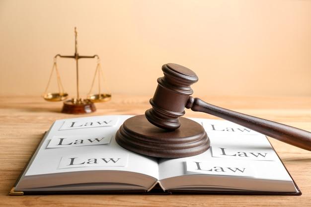 Marteau du juge et livre ouvert sur table en bois