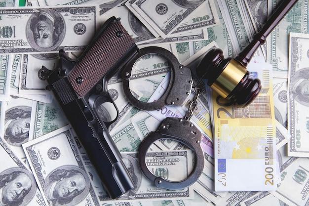 Marteau du juge, menottes, argent et arme à feu