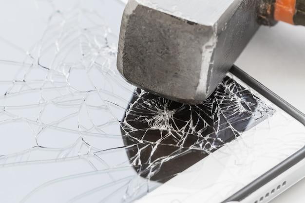 Un marteau est sur le smartphone avec un écran cassé.