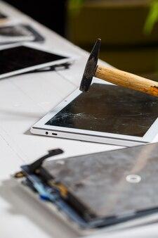 Le marteau frappe la tablette tactile cassée, suggérant qu'elle est sur le point de la remplacer. réparation de tablette de verre cassée
