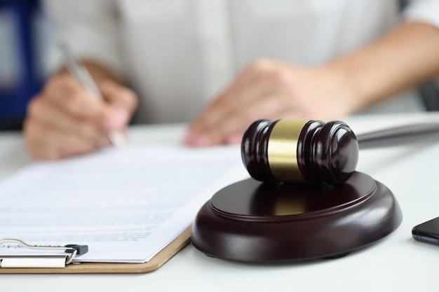 Marteau de juge en arrière-plan l'avocat signe des documents concept de profession de juge