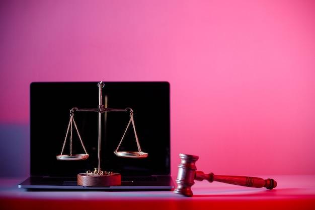 Marteau de juge et balance de la justice sur ordinateur portable.