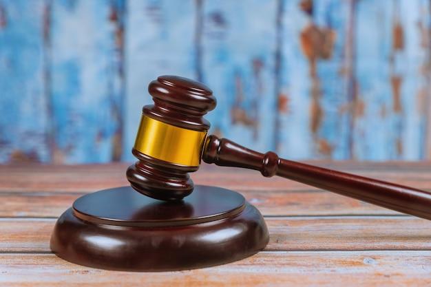 Marteau de juge en bois isolé sur fond en bois.