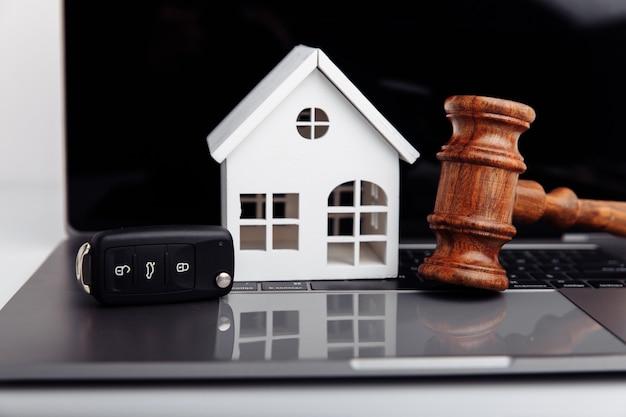 Marteau de juge en bois avec maison et clé de voiture aux enchères ou concept d'enchères