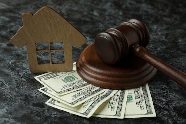 Marteau de juge, dollars et maison en bois sur table smokey noire
