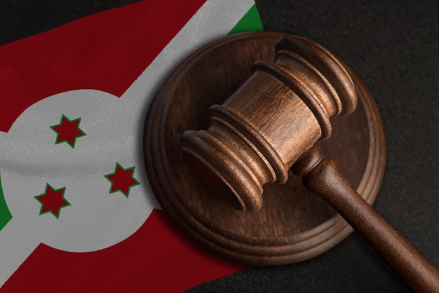 Marteau de juge et drapeau du burundi. droit et justice au burundi. violation des droits et libertés.