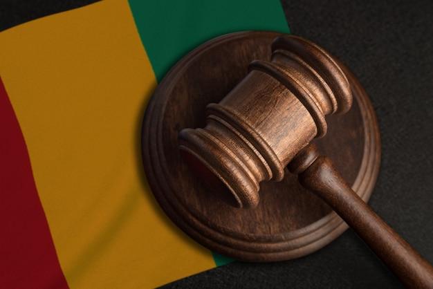 Marteau de juge et drapeau de la guinée. droit et justice en guinée. violation des droits et libertés.