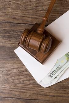 Marteau de juge sur enveloppe avec factures à table en bois
