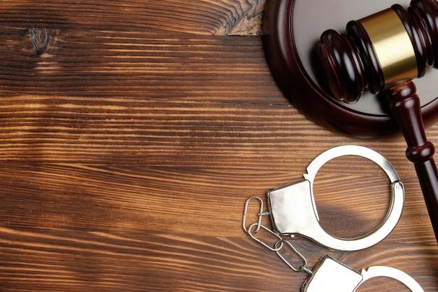 Marteau de juge avec des menottes sur fond de bois avec espace de copie