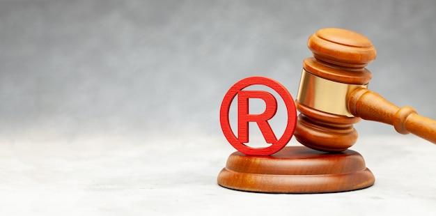 Marteau de juge et signe de marque rouge.