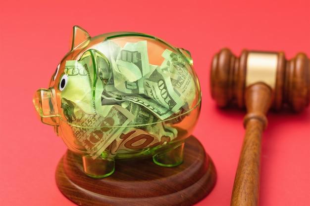 Marteau de juge et tirelire transparente pleine d'argent sur fond rouge