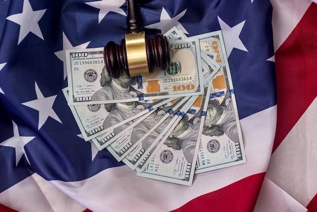 Marteau de juges avec des billets en dollars sur le drapeau américain