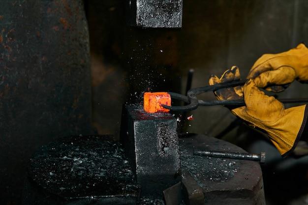 Le marteau de la machine écrase une billette chauffée au rouge tenue par un forgeron avec des pinces
