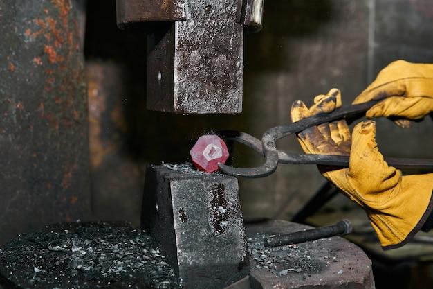 Le marteau de puissance se transforme en une sphère une pièce en métal chauffée au rouge tenue par un forgeron avec des pinces