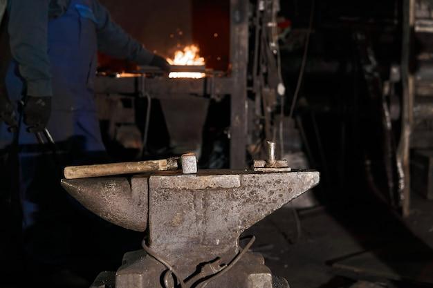 Le marteau repose sur l'enclume dans une forge traditionnelle tandis que le forgeron se rend au four