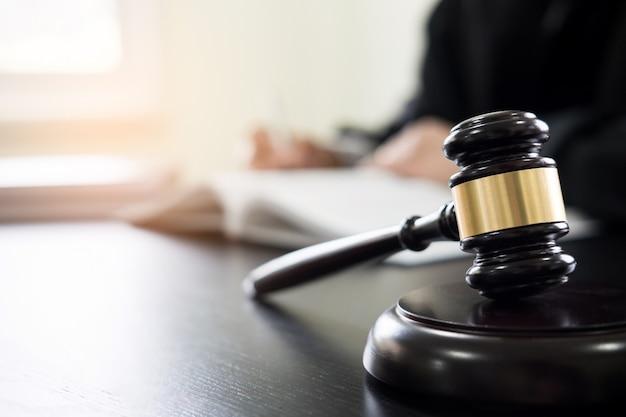 Marteau et soundblock du droit de la justice et avocat travaillant sur fond de bureau en bois.