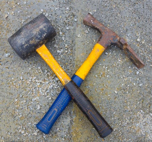 Marteaux croisés en caoutchouc et acier sur la surface en béton