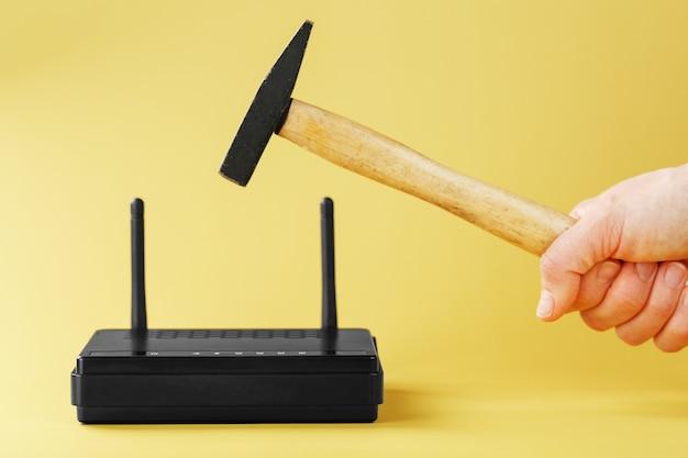 Martelez le routeur wi-fi pour destruction sur fond jaune.