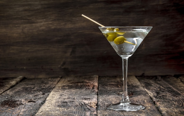 Martini aux olives sur une table en bois.