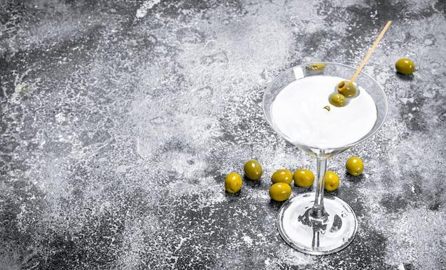 Martini aux olives sur une table rustique.
